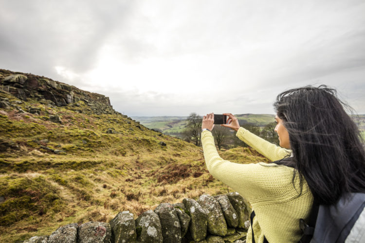 The landscape of the Peak District National Park, Derbyshire, woman taking a picture with her smartphone.