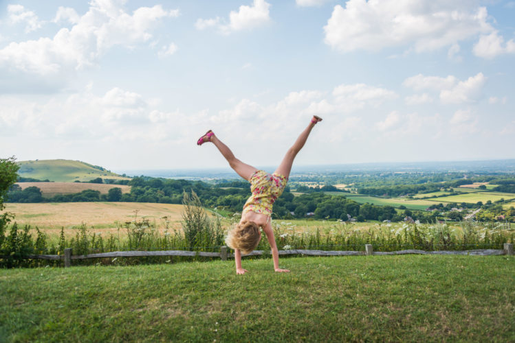 Young girl doing a cartwheel overlooking the South Downs.