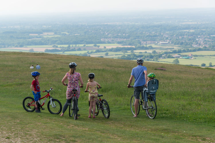 Family cycling during the day at Ditchling Beacon overlooking the South Downs.