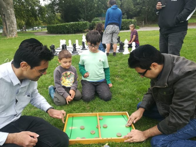 Two dads play a board game in the park as their children watch on. All socially distanced.