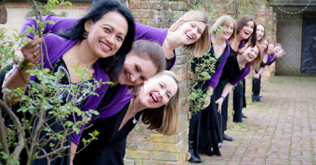 12 members of the Military Wives Choirs pose for a photo wearing choir outfits including a black dress and purple cardigan