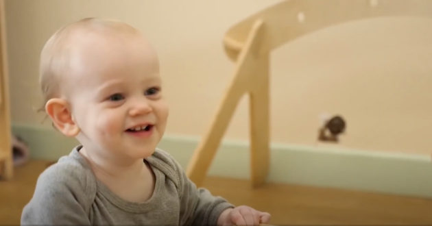 Image from Acorn childcare video of a smiling baby playing