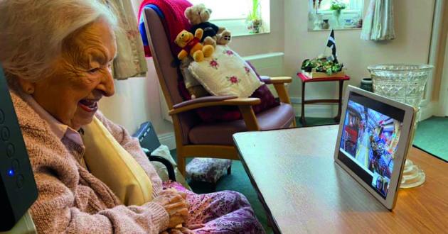 Irene Baker enjoying a virtual tour using an iPad, sat in her care home