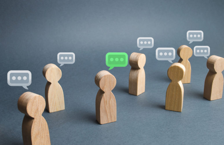 Wooden figures representing people with speech bubbles, representing them talking