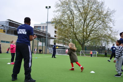 A young person is teaching children on how to play sports