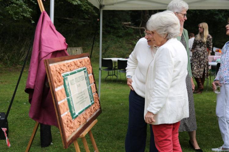 Volunteers look at special plaque