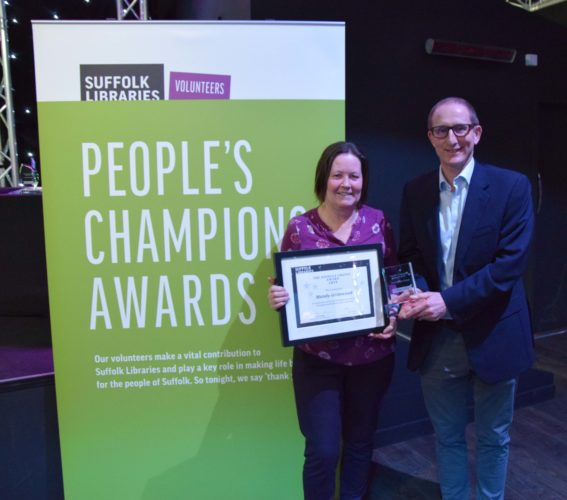 A picture of Mandy Grimwood, manager of Gainsborough Community Library, holding an award next to a colleague. She's holding an award for the People's Champion Award
